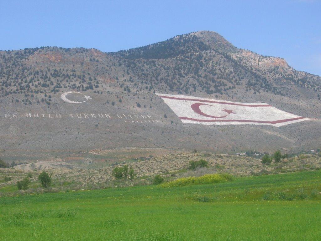 """Flaga TRNC, widoczna z Nikozji. Tekst obok mówi """"Jak szczęśliwy jest, kto mówi 'Jestem Turkiem!'"""", i jest cytatem z Mustafy Kemala Ataturka. (zdjęcie (c) Mustafa Baykan, via panoramio.com)"""